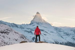 Guy Standing At Edge of Cliff in Snow Looking at Mountain In Distance