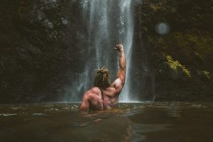 Man Standing Facing Waterfall in Water with Shirt Off