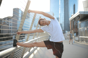 Guy Stretching on Railing With Cityscape In Background