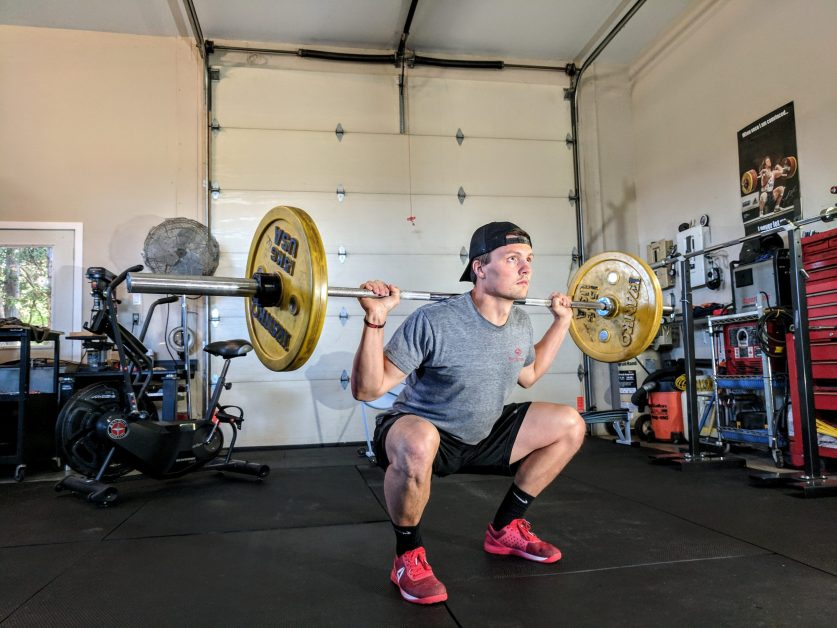 Guy Squatting with Barbell In Garage Gym