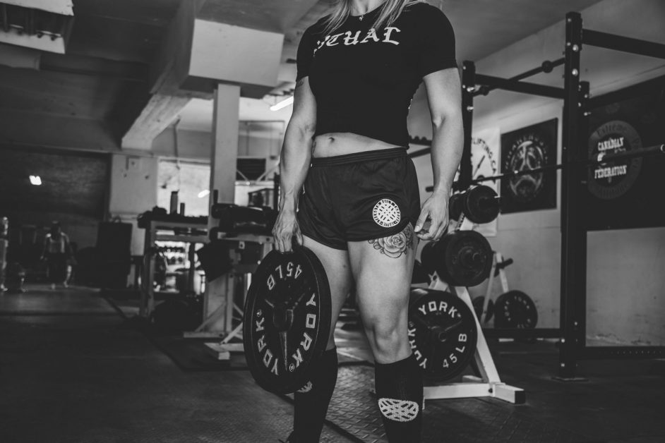 Woman in Gym with Strong Quads Holding Weight Plate in Black and White Photo