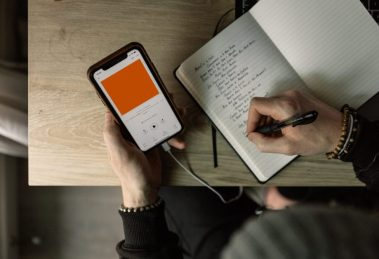 Guy Listening to Audiobook on Smart Phone and Taking Notes in Journal