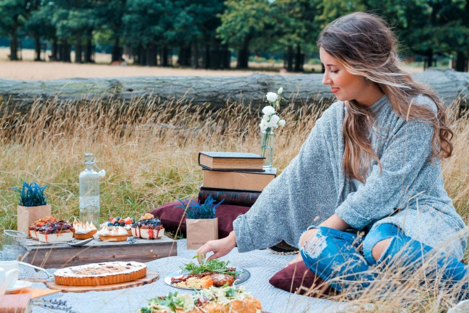 Woman Sitting on Blanket Eating Picnic in Field