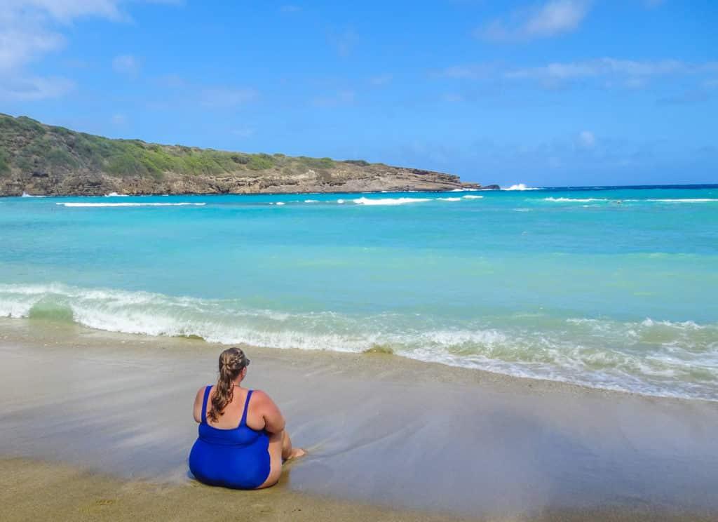 Girl sitting on the beach in Oahu, Hawaii
