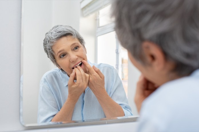 Mature beautiful woman cleaning her teeth with floss in bathroom