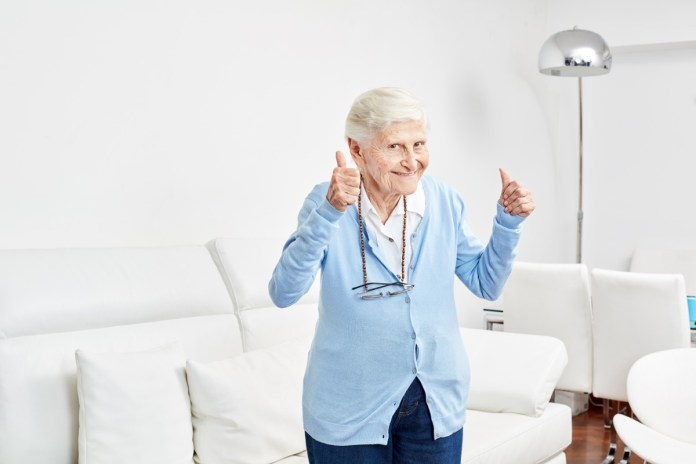 Optimistic old woman holds the thumbs up full of joy and vitality