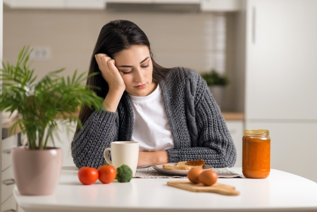 Displeased young woman doesn't want to eat her breakfast