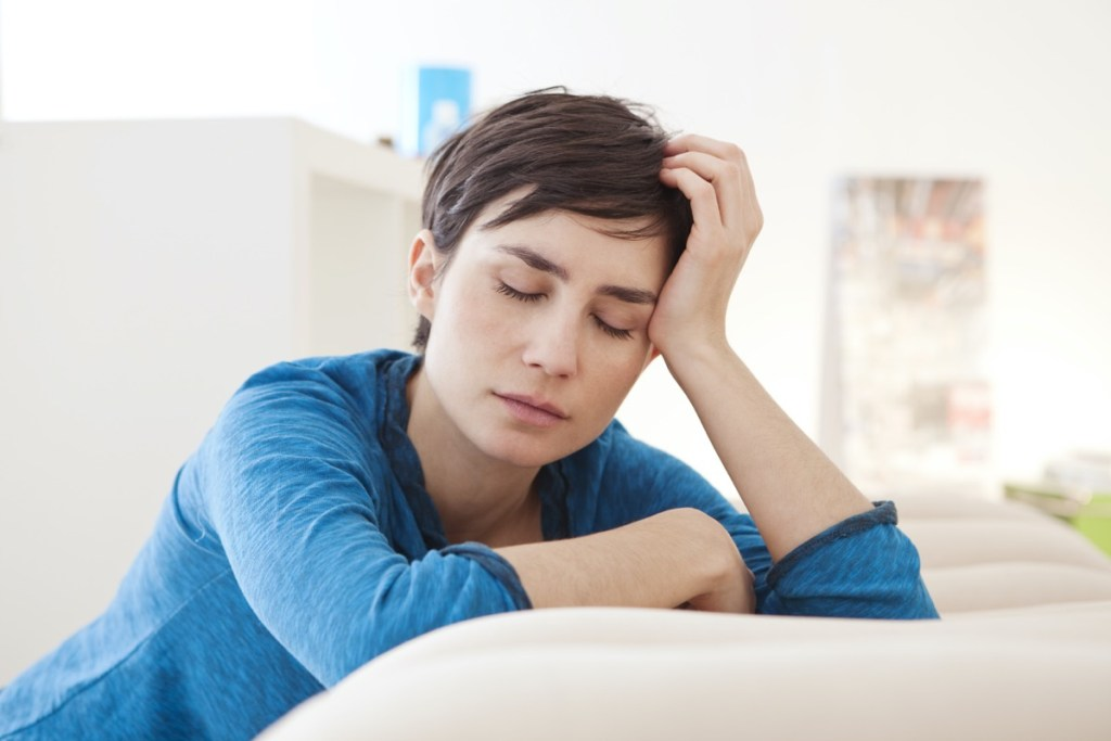 Tired woman with closed eyes leaning over coach at home