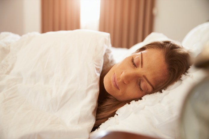 Woman Asleep In Bed As Sunlight Comes Through Curtains