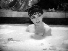 A bathing Claudette Colbert
