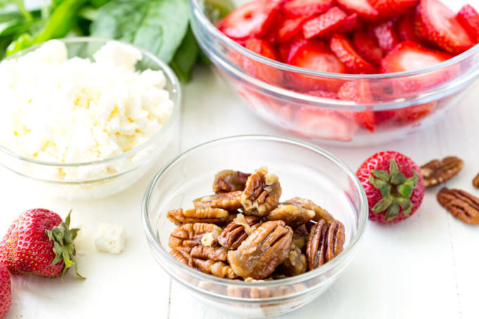 Pecans, strawberries, and cheese in separate bowls.