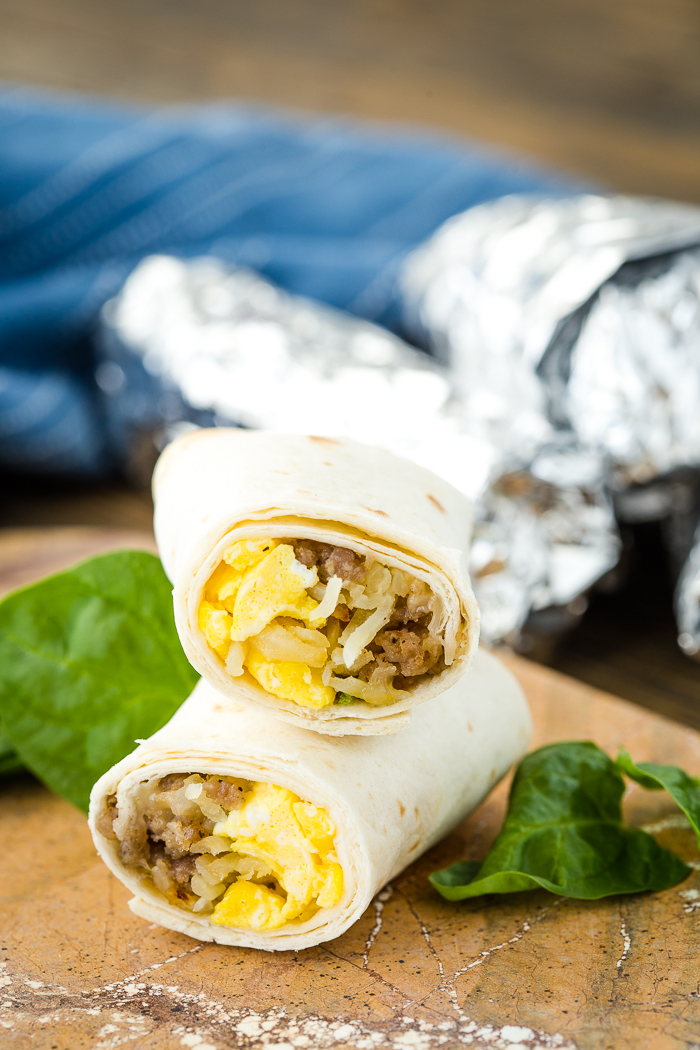 A cut breakfast burrito, stacked on top of each other, foil wrapped burrito in the background.