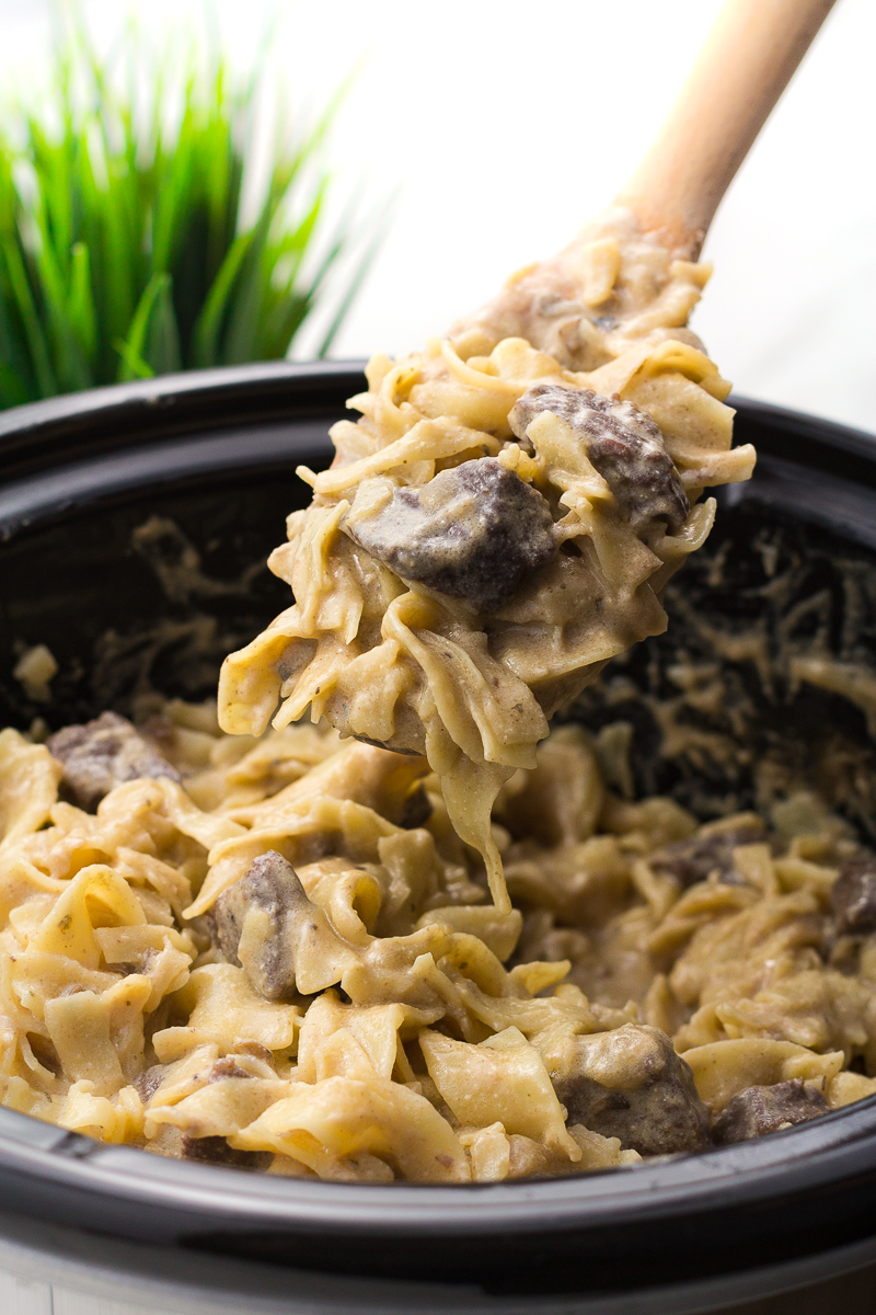 Slow cooker beef stroganoff in a crock pot with a spoon scooping some out