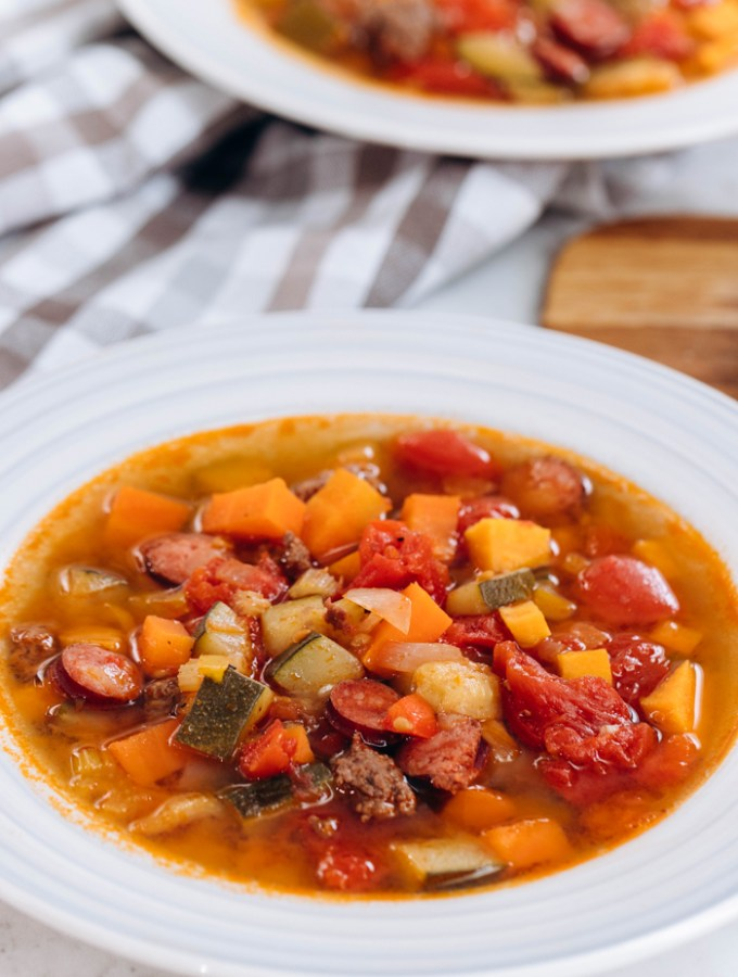 A big bowl of beef and vegetable soup, in a white bowl