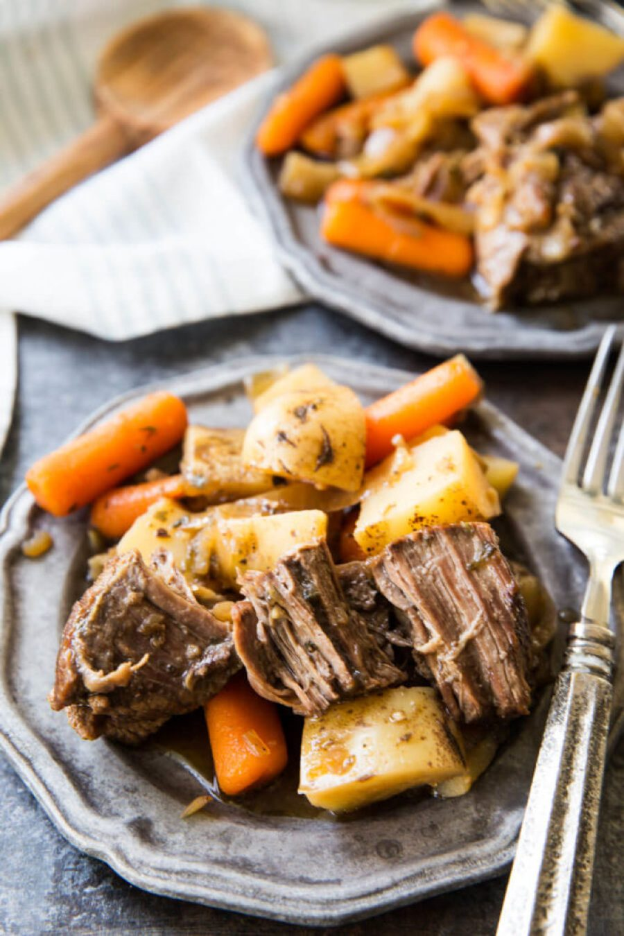 Crock pot chuck roast with potatoes and carrots 2 silver plates with a fork over one plate