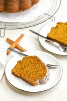 Two white plates each holding a piece of pumpkin cake, a few sticks of cinnamon, and forks