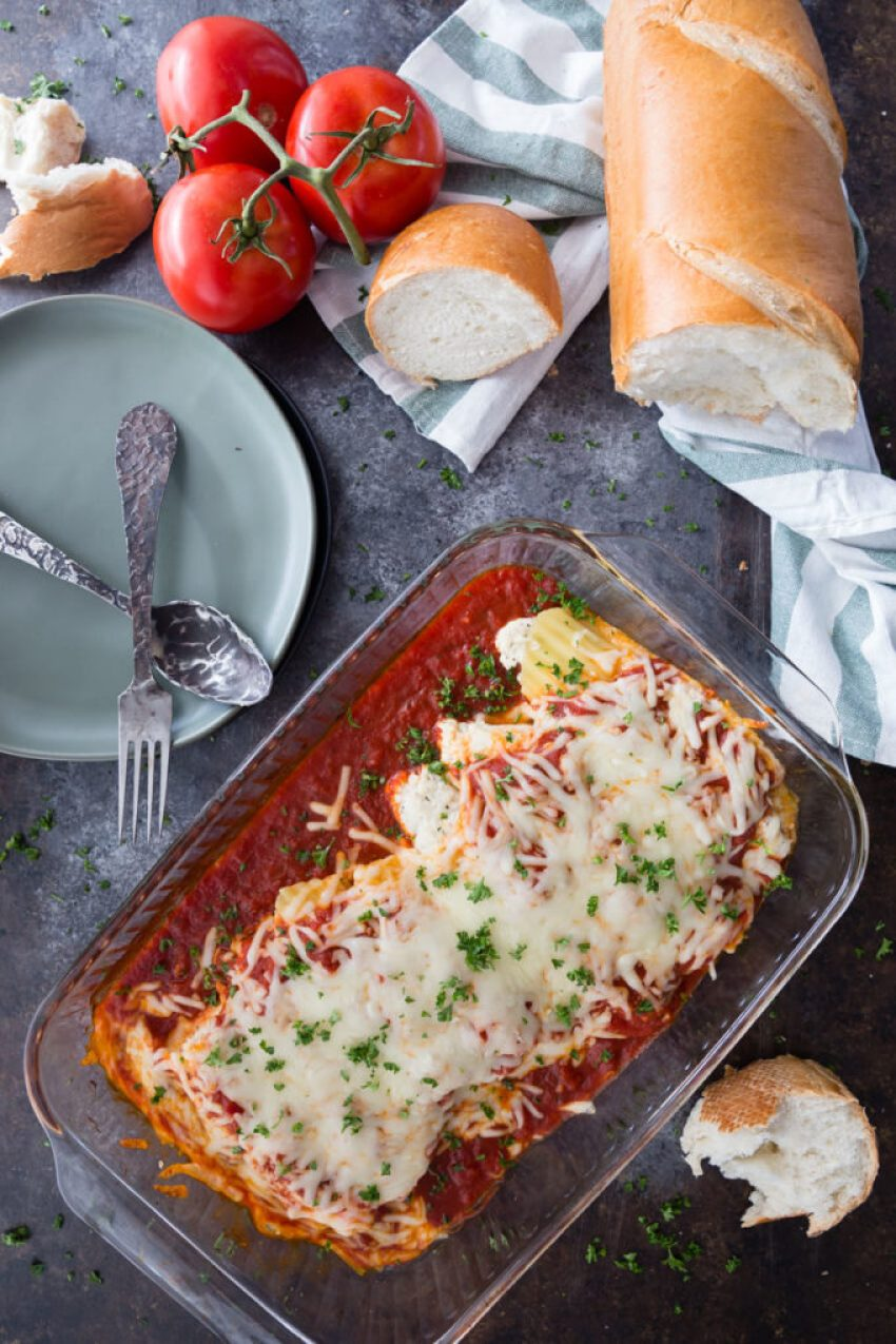 A glass baking dish of stuffed manicotti with French bread and fresh tomatoes