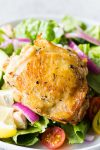 Baked Greek Chicken Thighs on a bed of lettuce