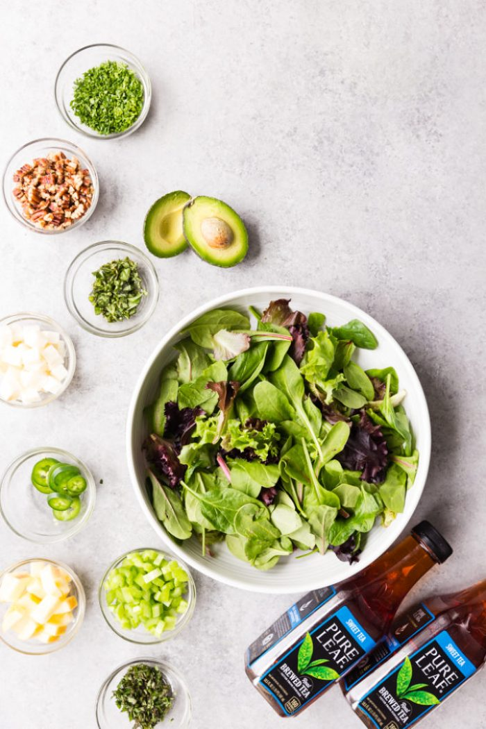 Grilled Chicken Salad with all the ingredients around the big bowl of lettuce.