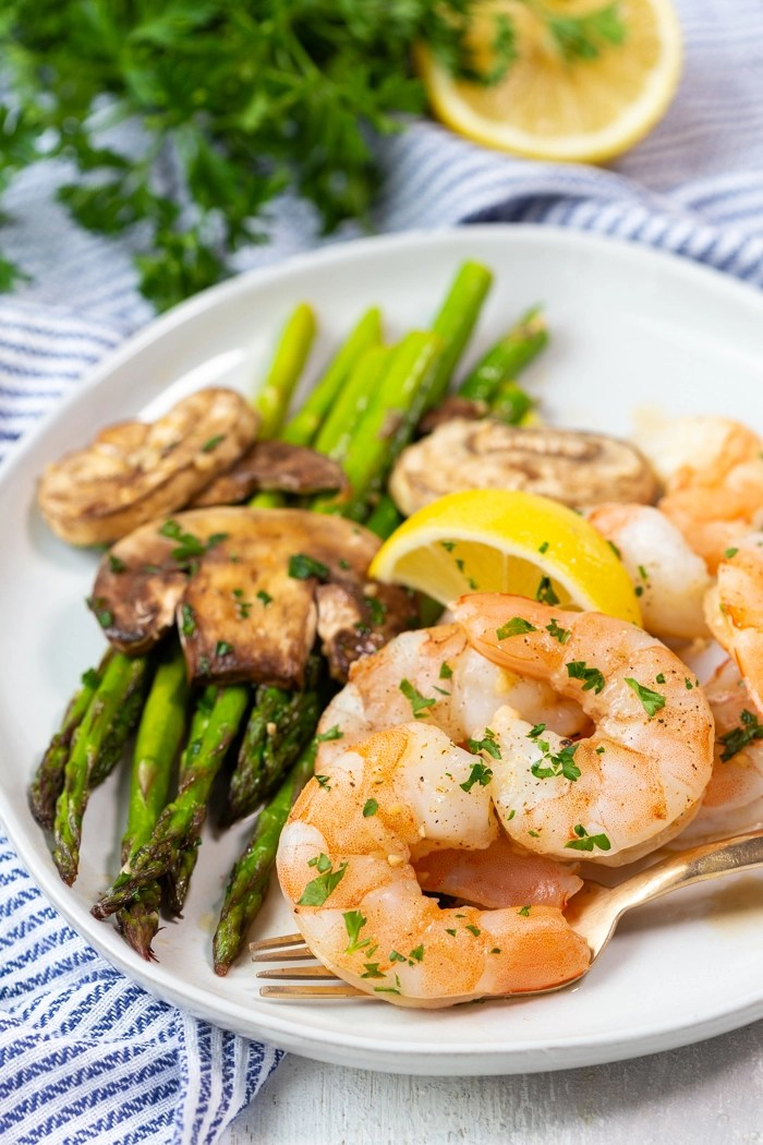 A plate with asparagus, mushrooms, and honey garlic shrimp from a low calorie sheet pan dinner