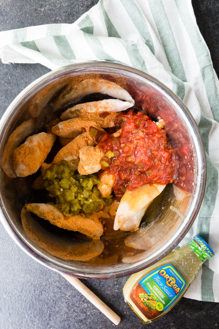 salsa and seasonings on top of frozen chicken in a metal bowl