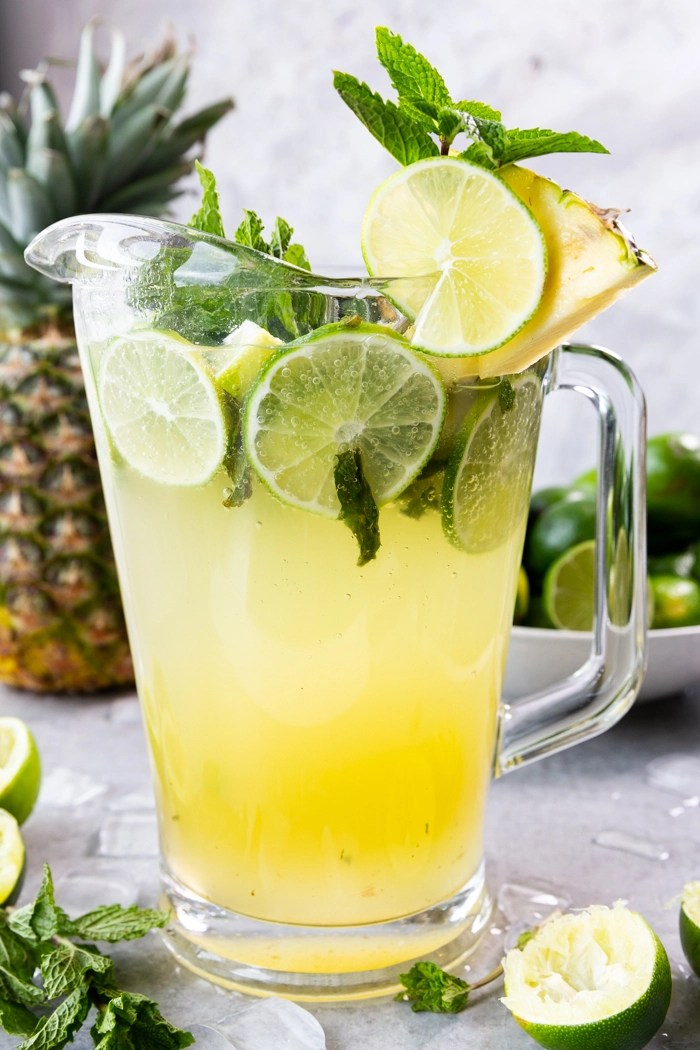 Pineapple Mojito in a pitcher with limes, mint, and pineapple juice