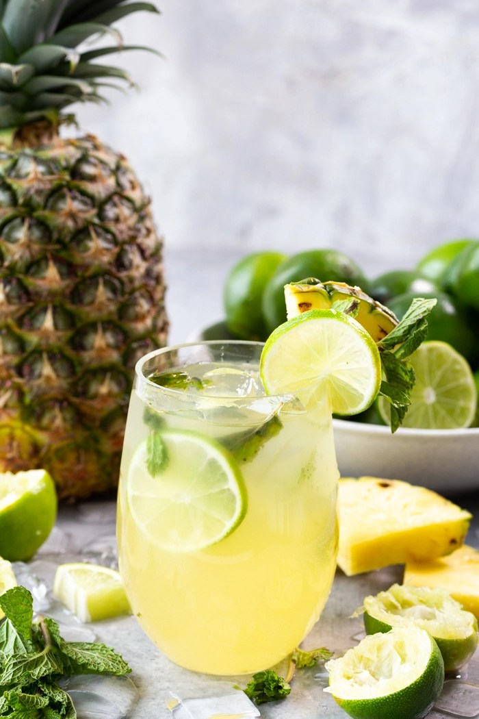 A glass of pineapple mojito with a pineapple and a bowl of limes in the background