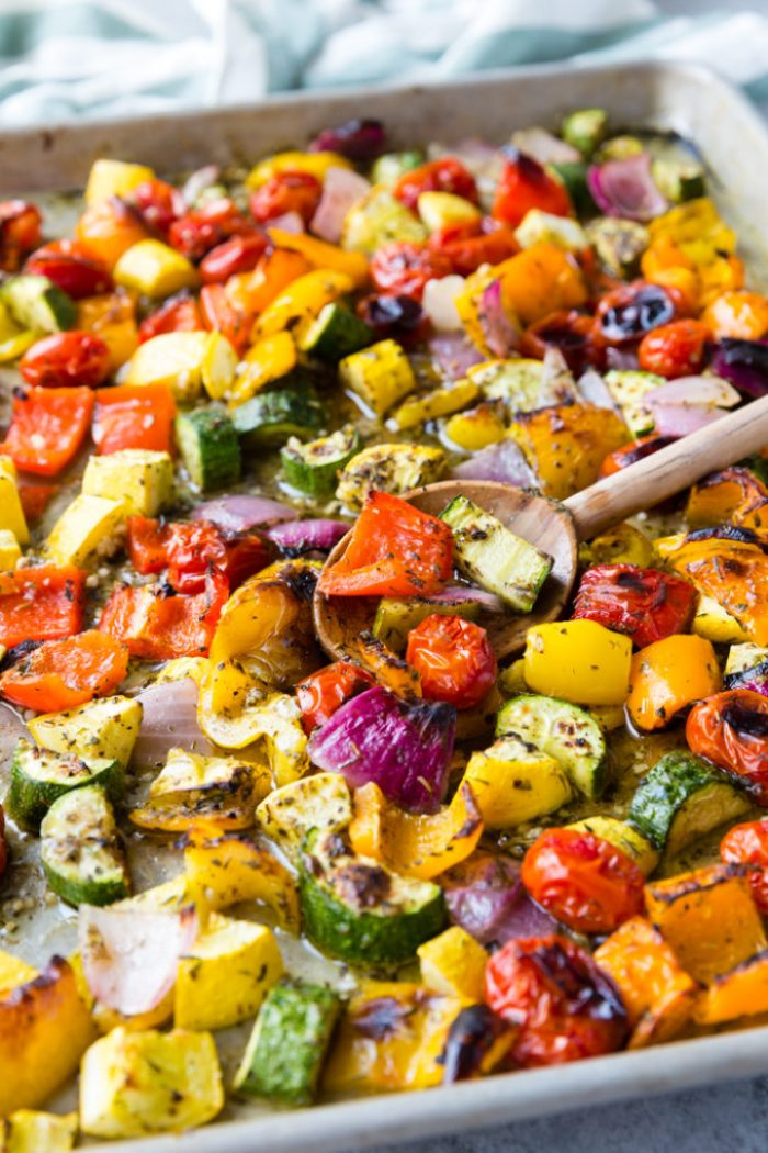 Roasted Greek Vegetables on a sheet pan with a wooden spoon.