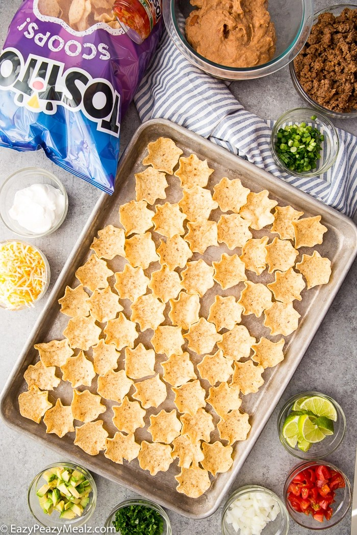 A baking tray covered in Tostitos Scoops with the fixings for taco bites around it.