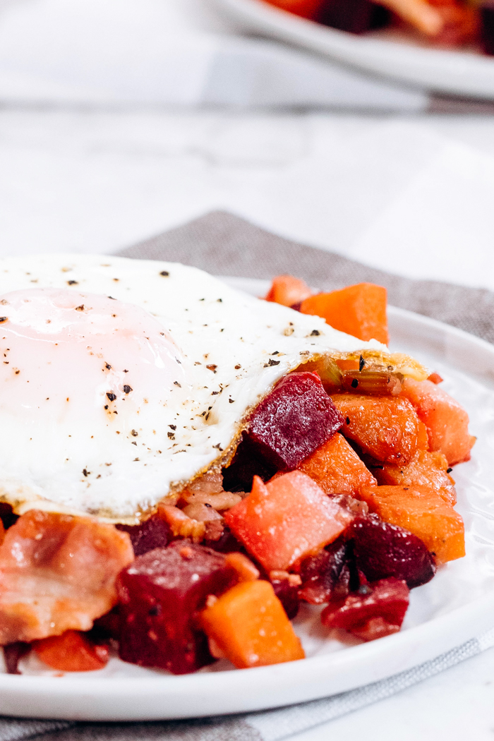 A white plate topped with veggie hash with bacon, and topped with a fried egg.