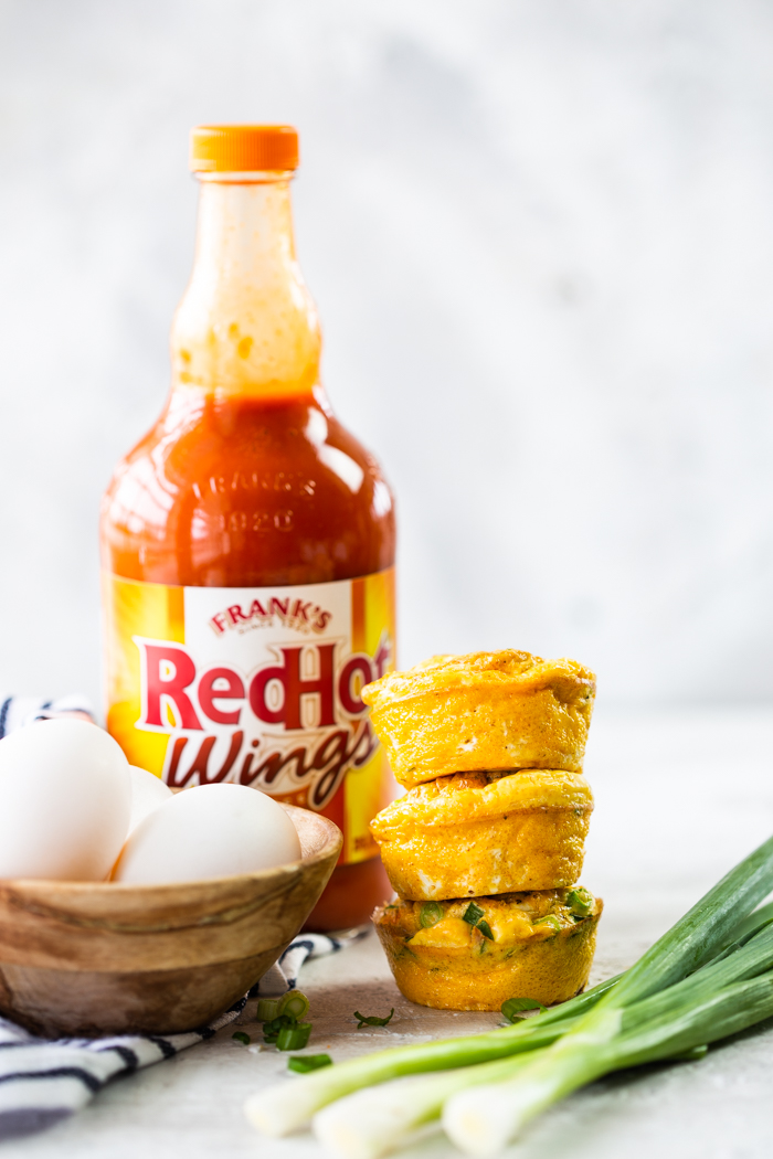 buffalo chicken egg muffins stacked on top of each other with whole eggs in a cup to the side. franks red hot wings sauce in the background