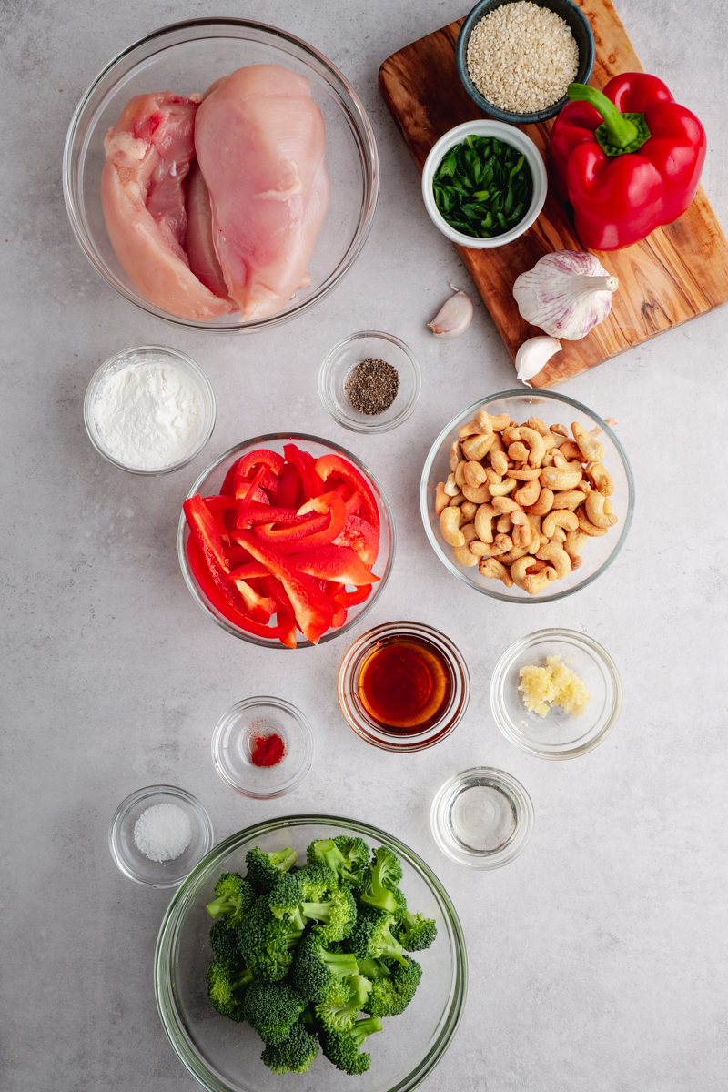 Portion cups with all the ingredients needed for cashew chicken, including raw chicken, vegetables, cashews. There is a cutting board in the top right hand cornder with more ingredients on top.