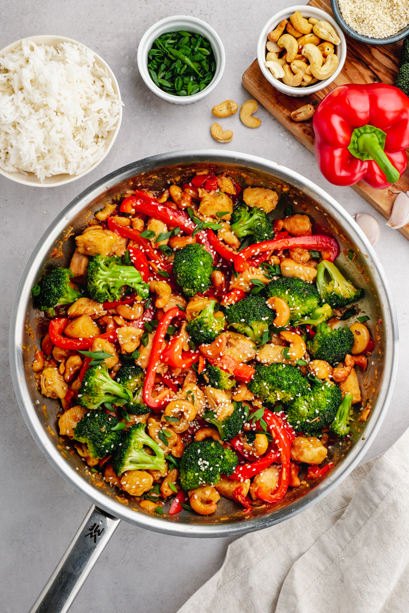 A stainless steel saute pan with cashew chicken inside, a bowl of rice, garnish, and a cutting board with cashews and red bell pepper on the sides.