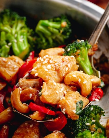 A stainless steel pan full of cashew chicken with a spoon ful elevated partially out of the pan.