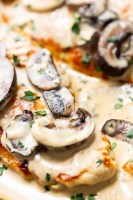 Creamy chicken marsala in a skillet with mushrooms and fresh herbs