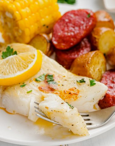 Roasted Halibut Sheet Pan Dinner on white plate with fork into a piece.