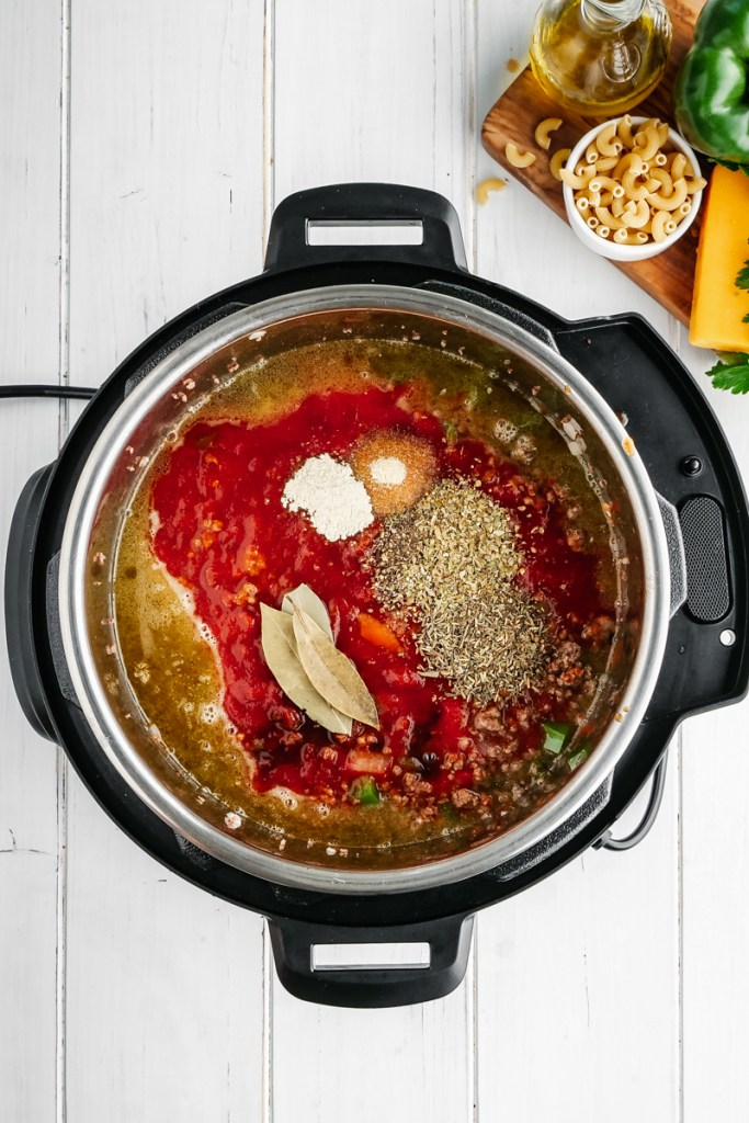 An instant pot with the beginnings of American Goulash, spices, ground beef, onions, and peppers