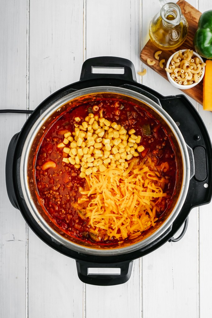 An instant pot with tomato sauce, corn, cheese, and macaroni, to make American Goulash.