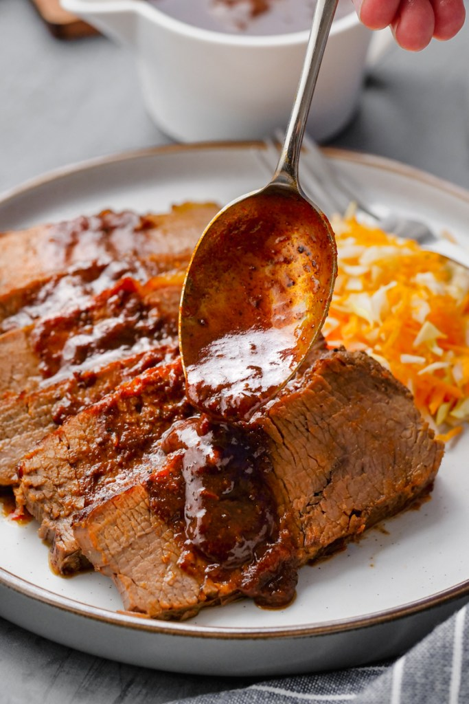 instant pot brisket on white plate with sauce and salad