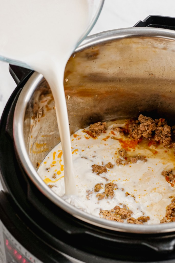 Pouring milk mixture into the pressure cooker sausage gravy recipe