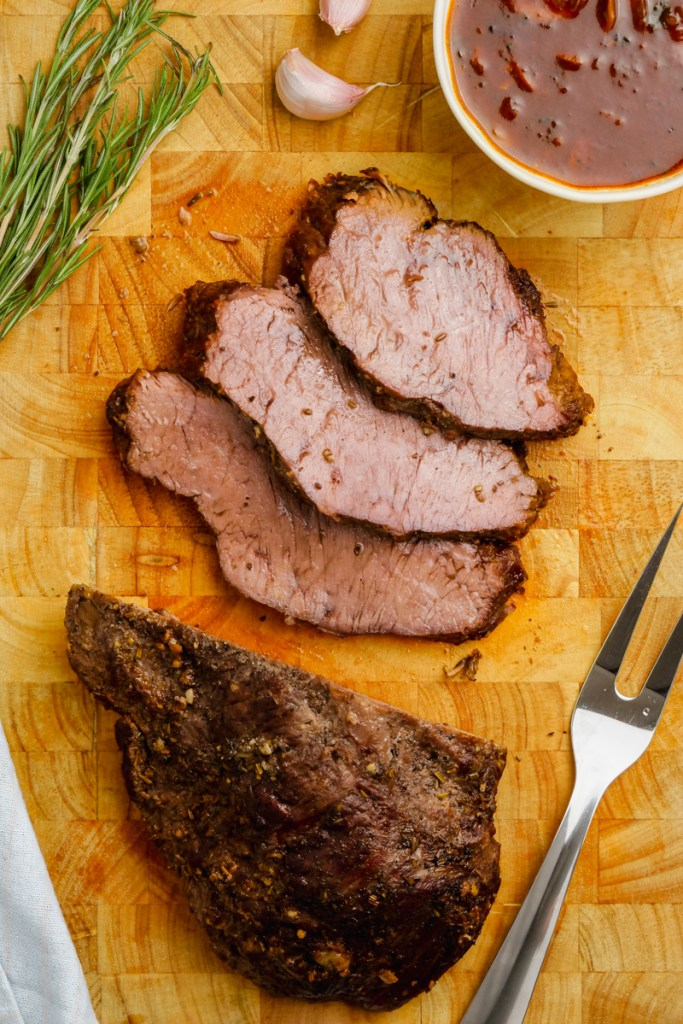 Instant Pot Sirloin Roast Beef with Mushroom Sauce on a cutting board with basil to the side