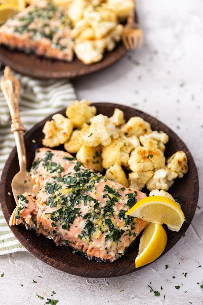 lemon parsley garlic salmon with cauliflower on a wooden plate with lemon wedges