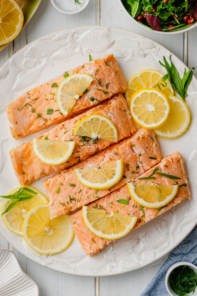 A white plate with oven poached salmon and lemons and dill