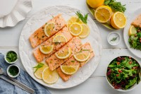 salmon with limes on top and a white plate underneath