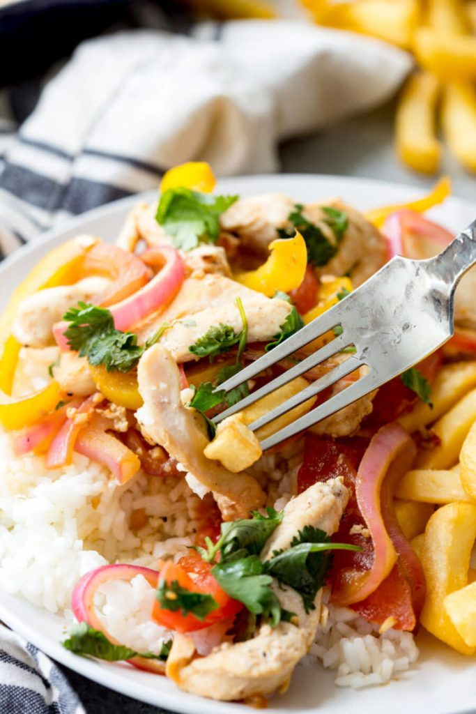 Pollo Saltado a Peruvian chicken stir fry that is served with fries and rice.