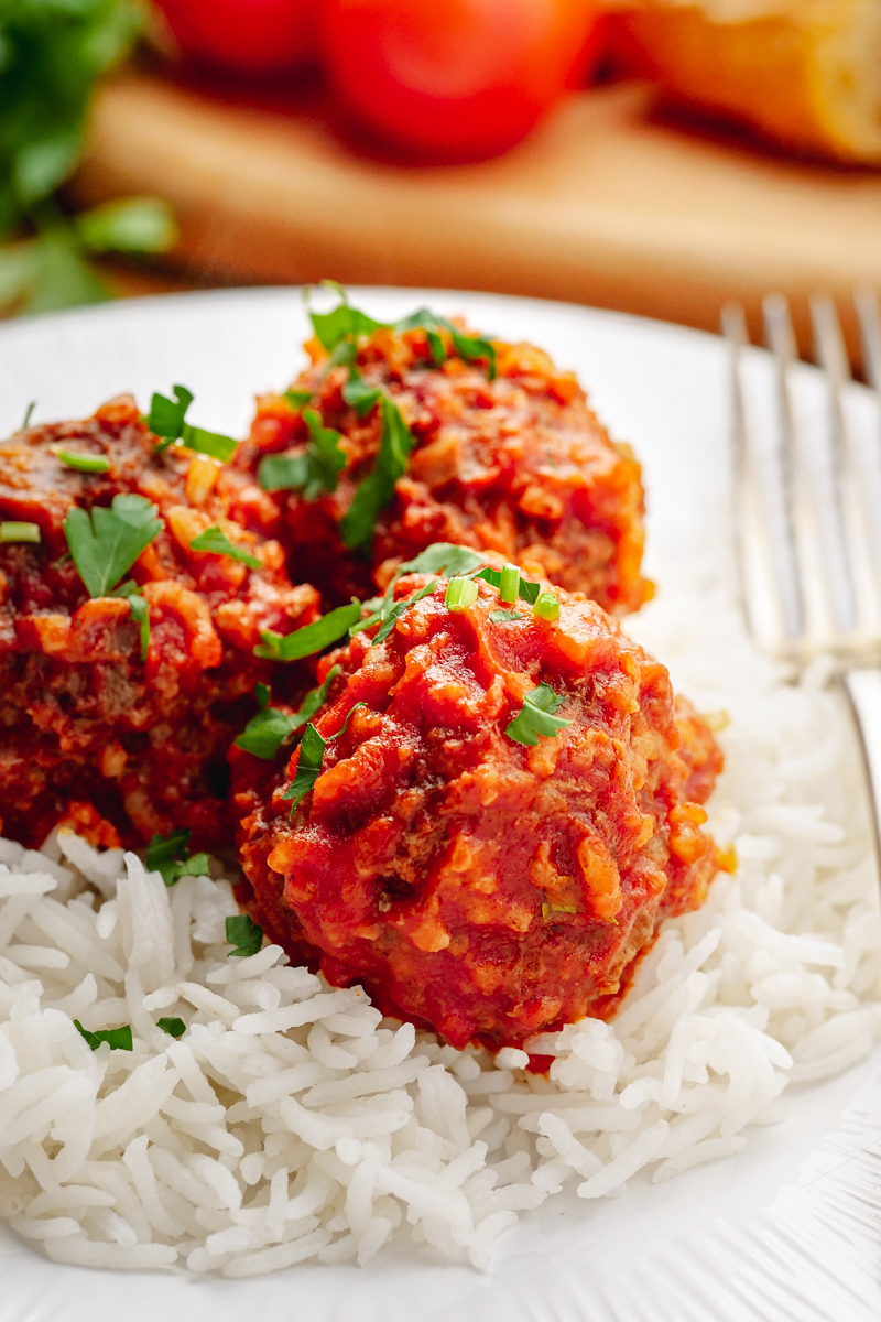 Porcupine meatballs on a bed of rice, on a white plate, fork on the side.