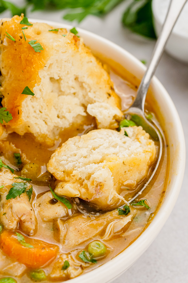 A white bowl with chicken and dumplings, a spoon scooping