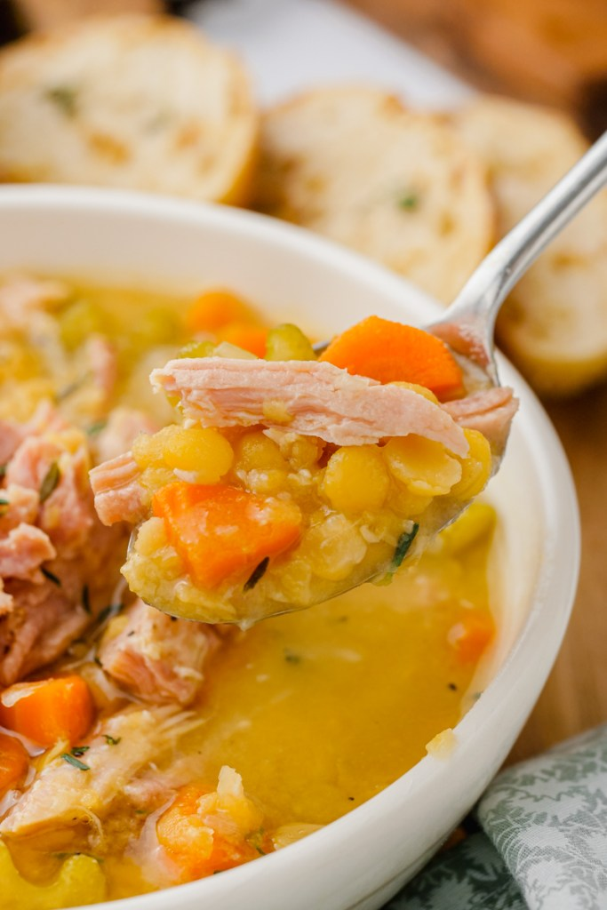 Split pea soup in white bowl with spoon in it with bread to the side