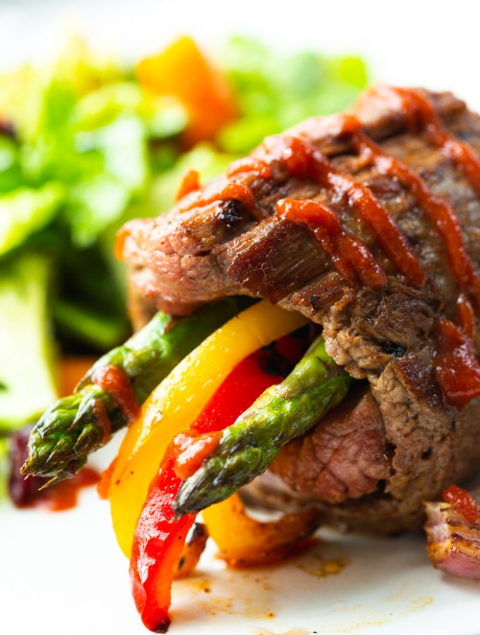 Steak roll ups- these low carb steak fajitas roll ups are on a white plate with a green salad in the background