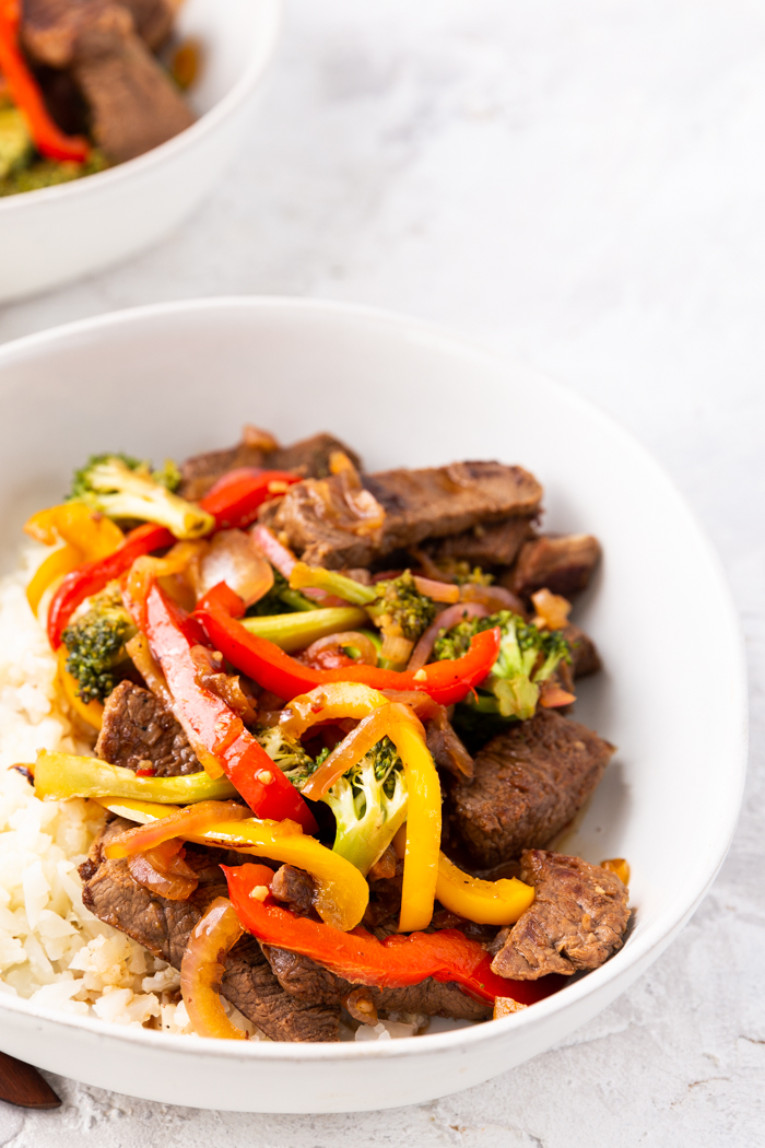 view of steak stir fry in the white bowl at a closer birds eye angle